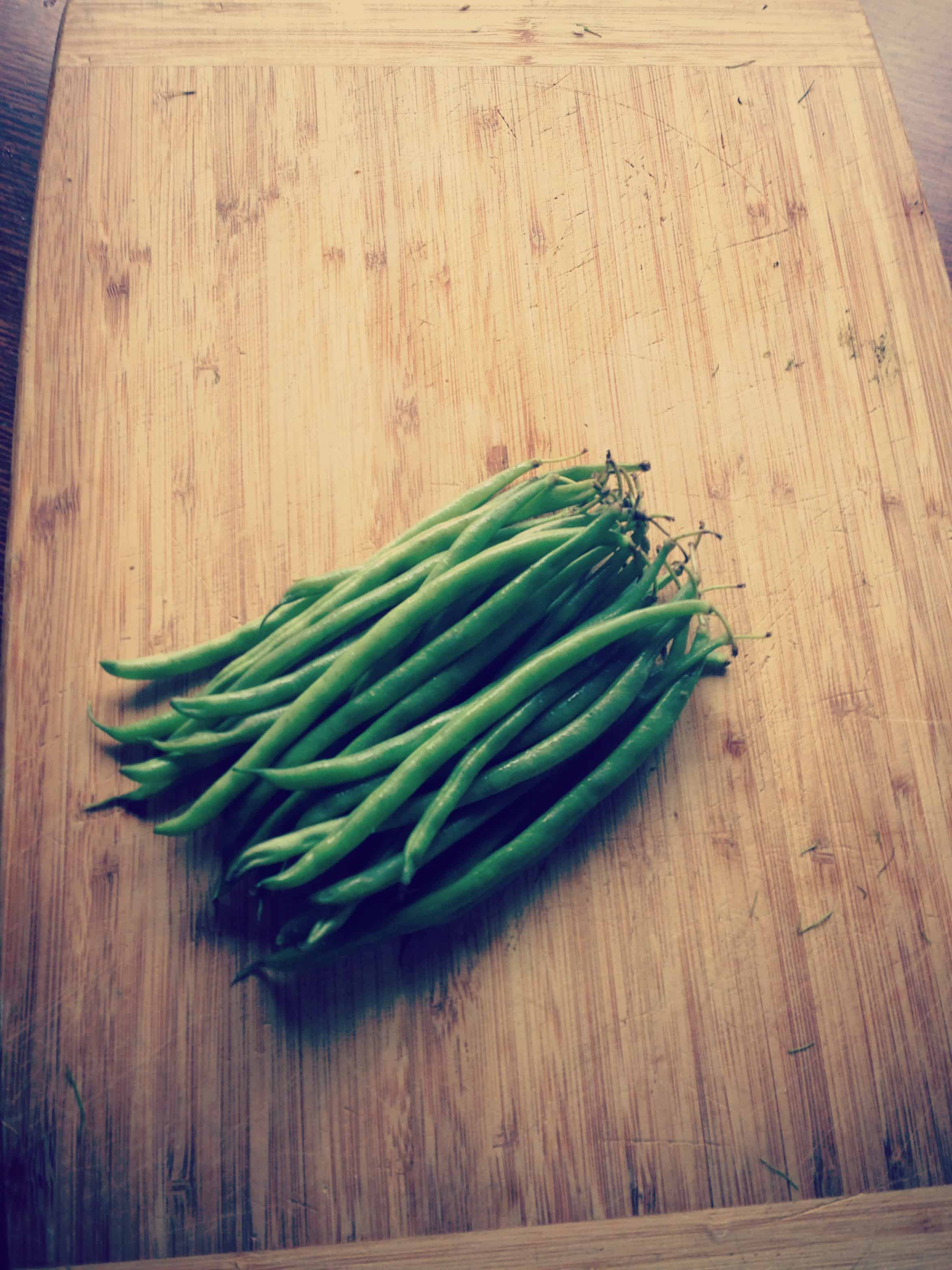 A pile of fresh green beans on a wood cutting board.