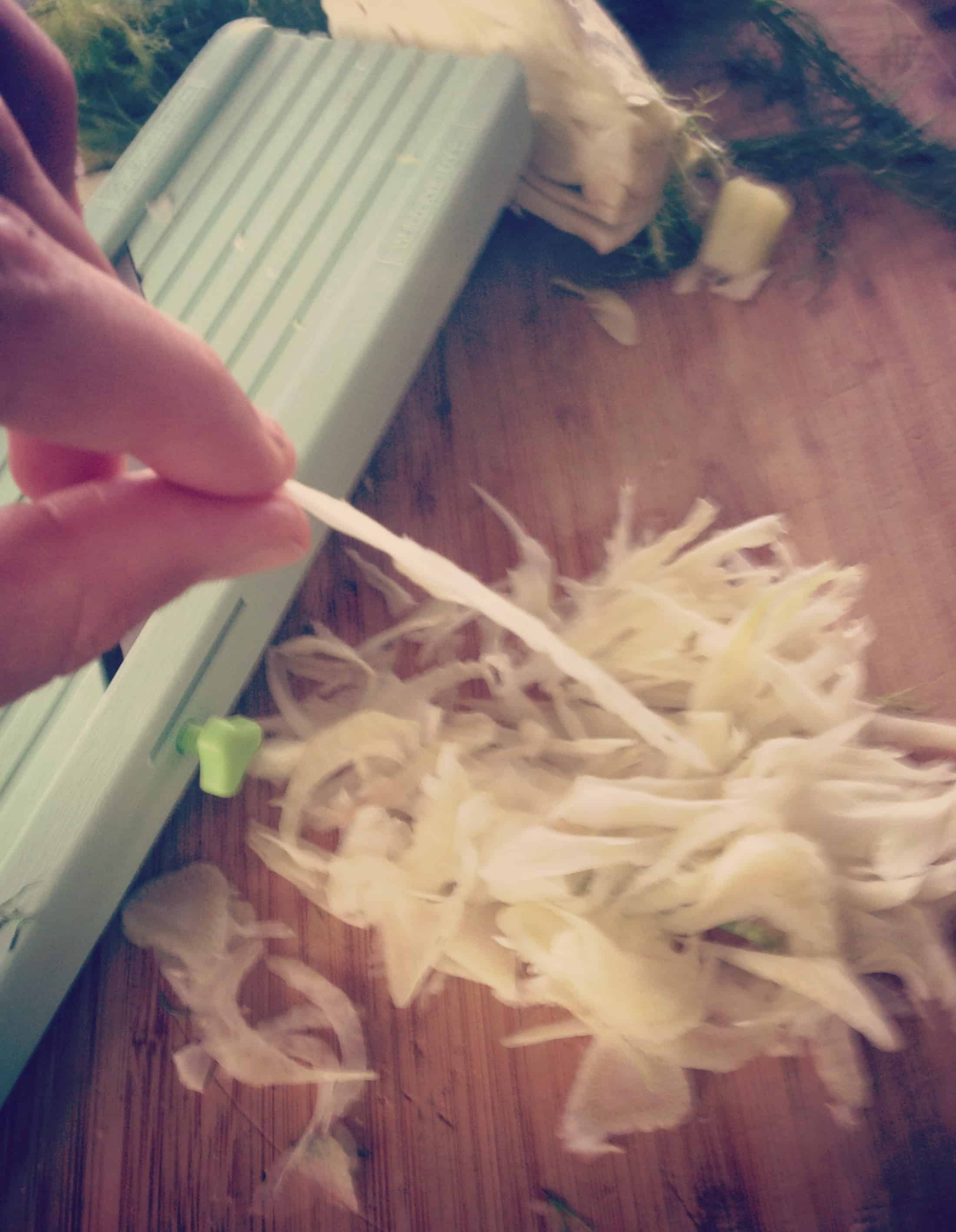 A hand holding a shaved slice of fennel in front of a mandoline.