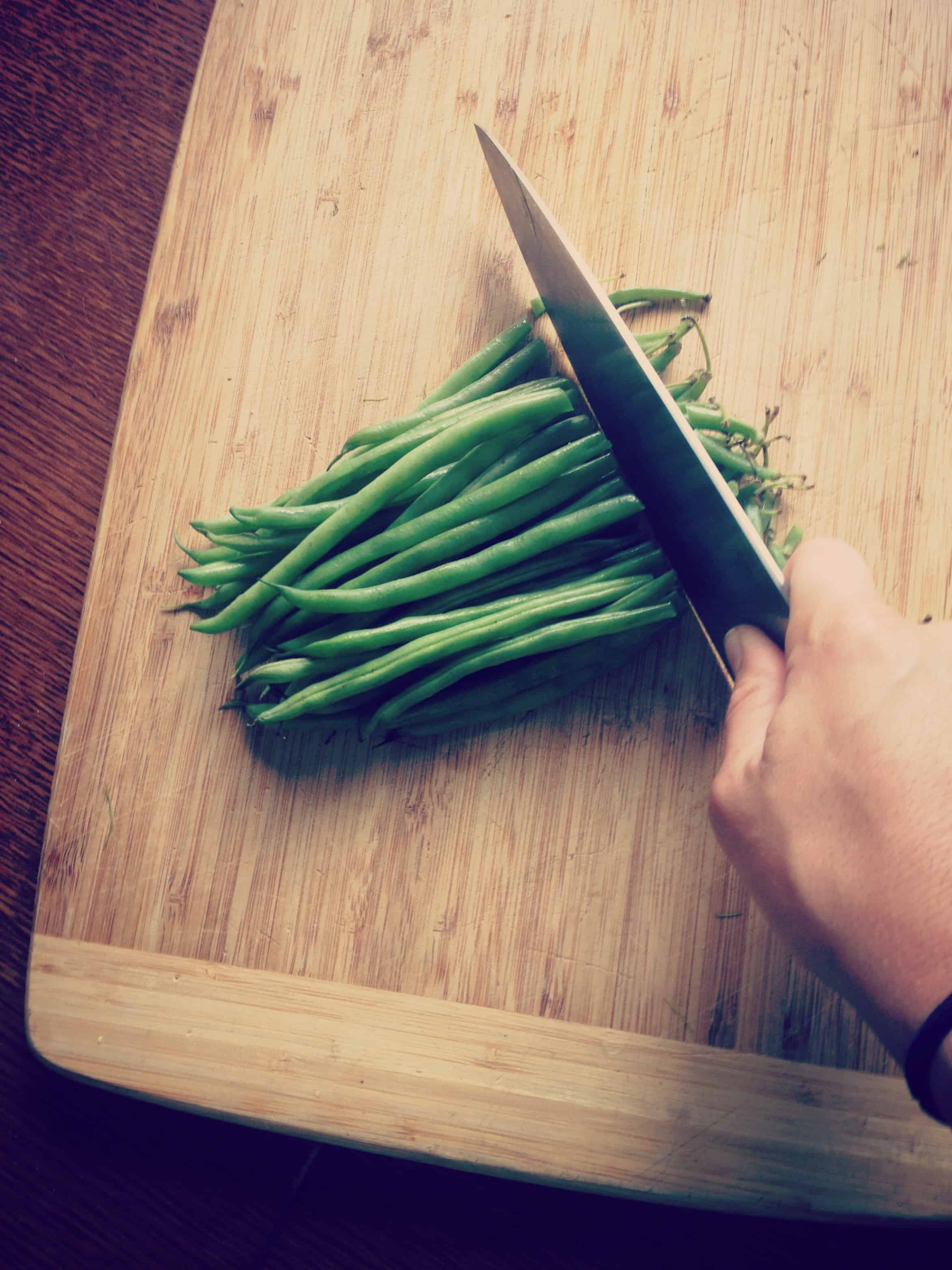 A knife ready to cut off one inch of green beans on a wooden cutting board.