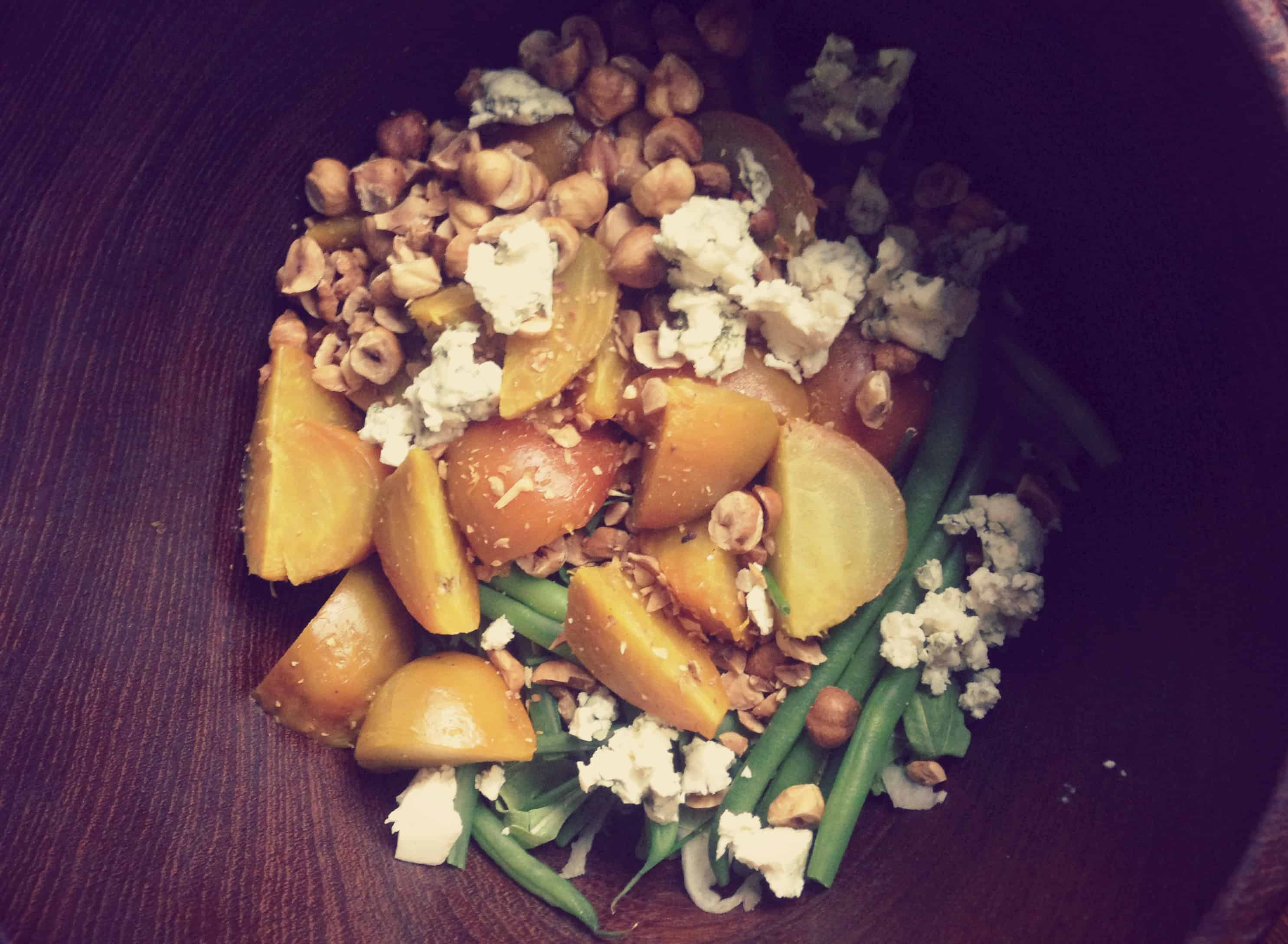 A salad of golden beets, blue cheese, green beans, and hazelnuts in a wood bowl.