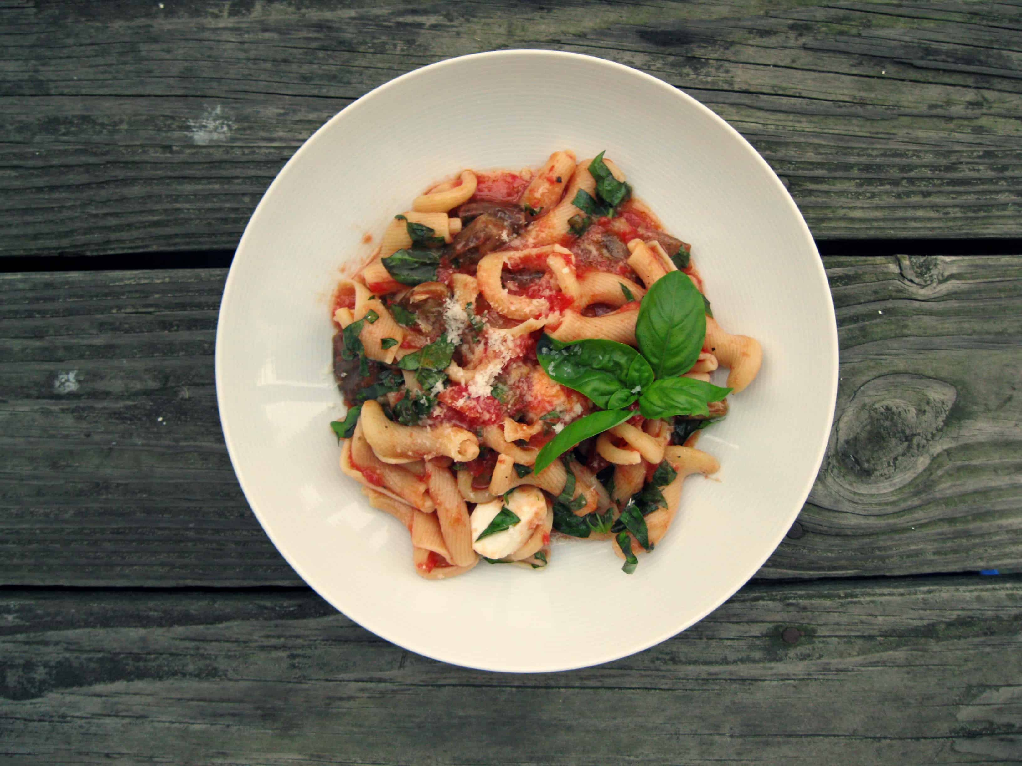 Top view of a bowl of pasta with eggplant and tomato.