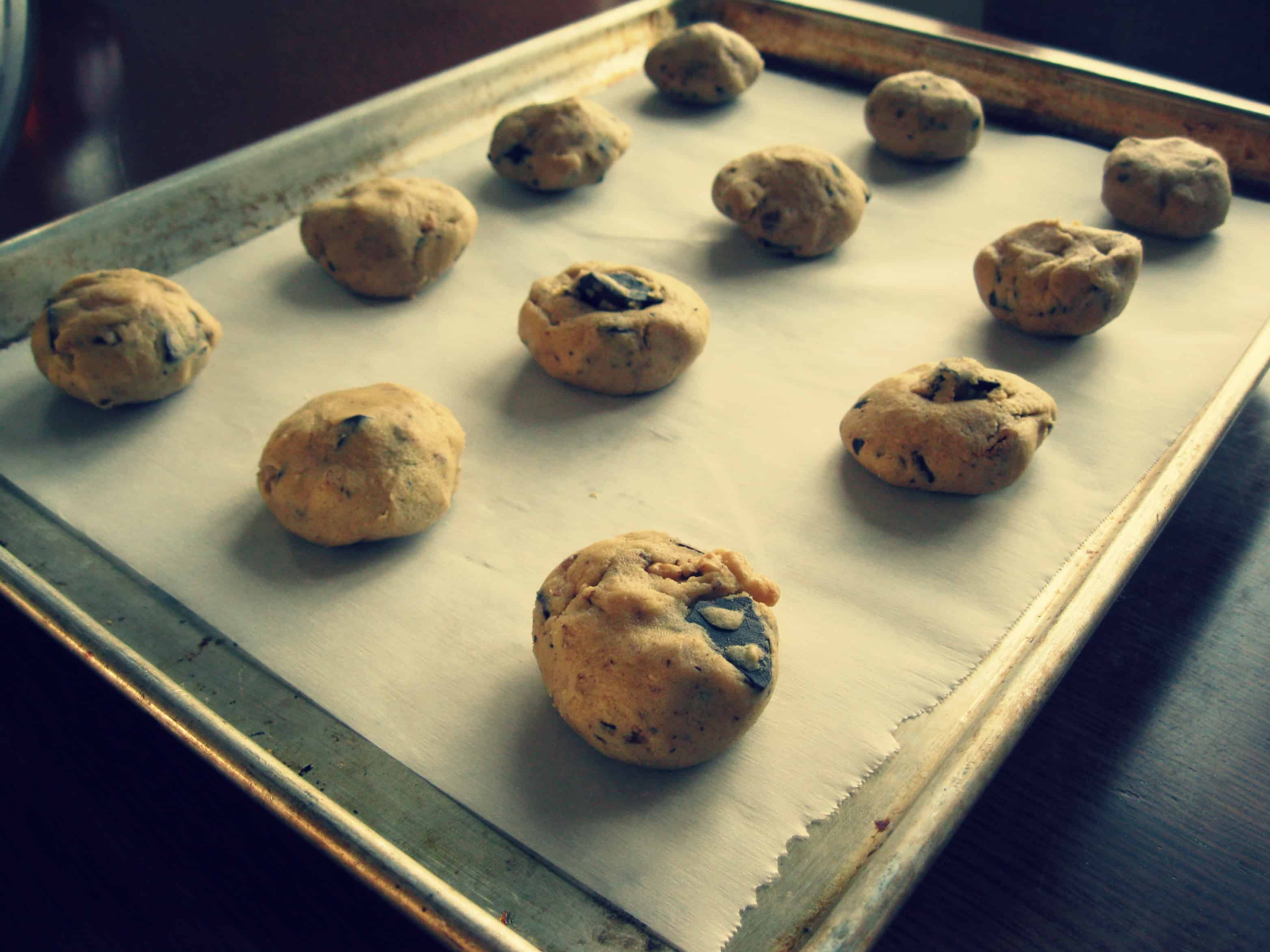 Chocolate chip cookie dough balls sitting on a parchment lined baking sheet.