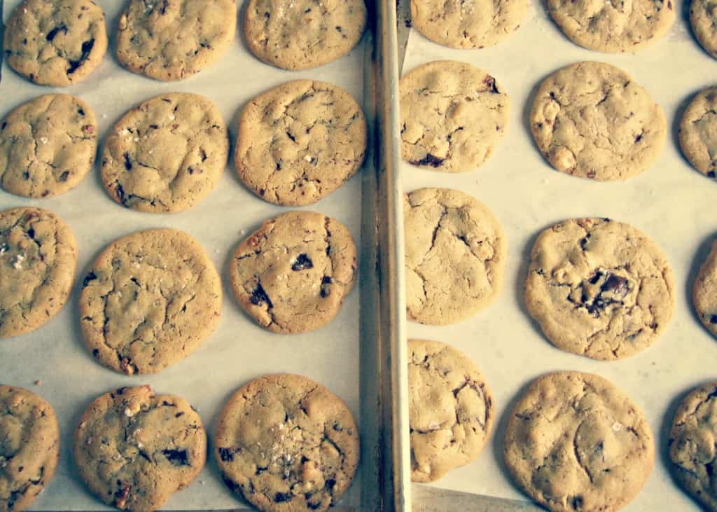 Two parchment lined baking sheets filled with baked chocolate chip cookies.