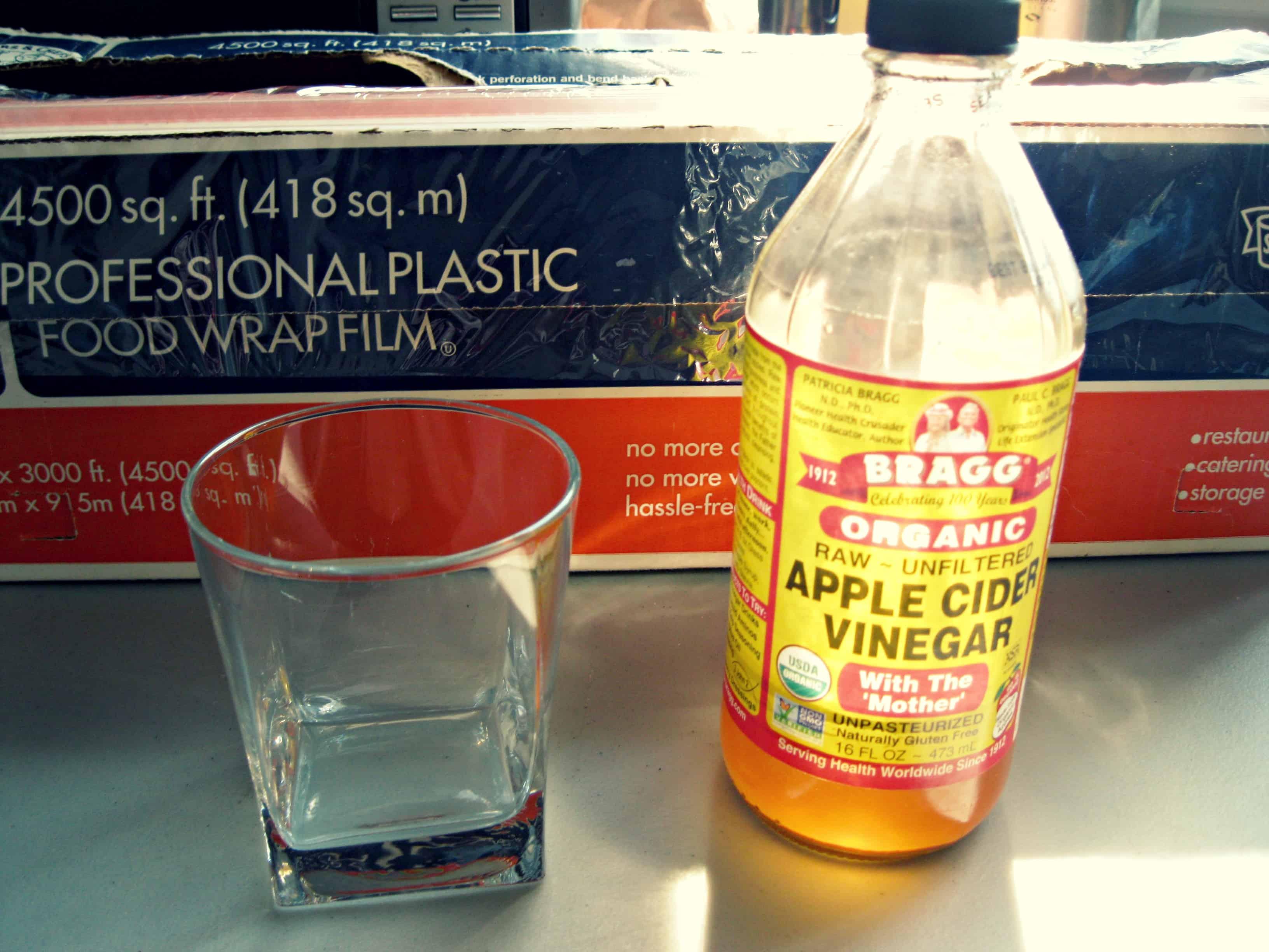 A jar of apple cider vinegar next to an empty glass.