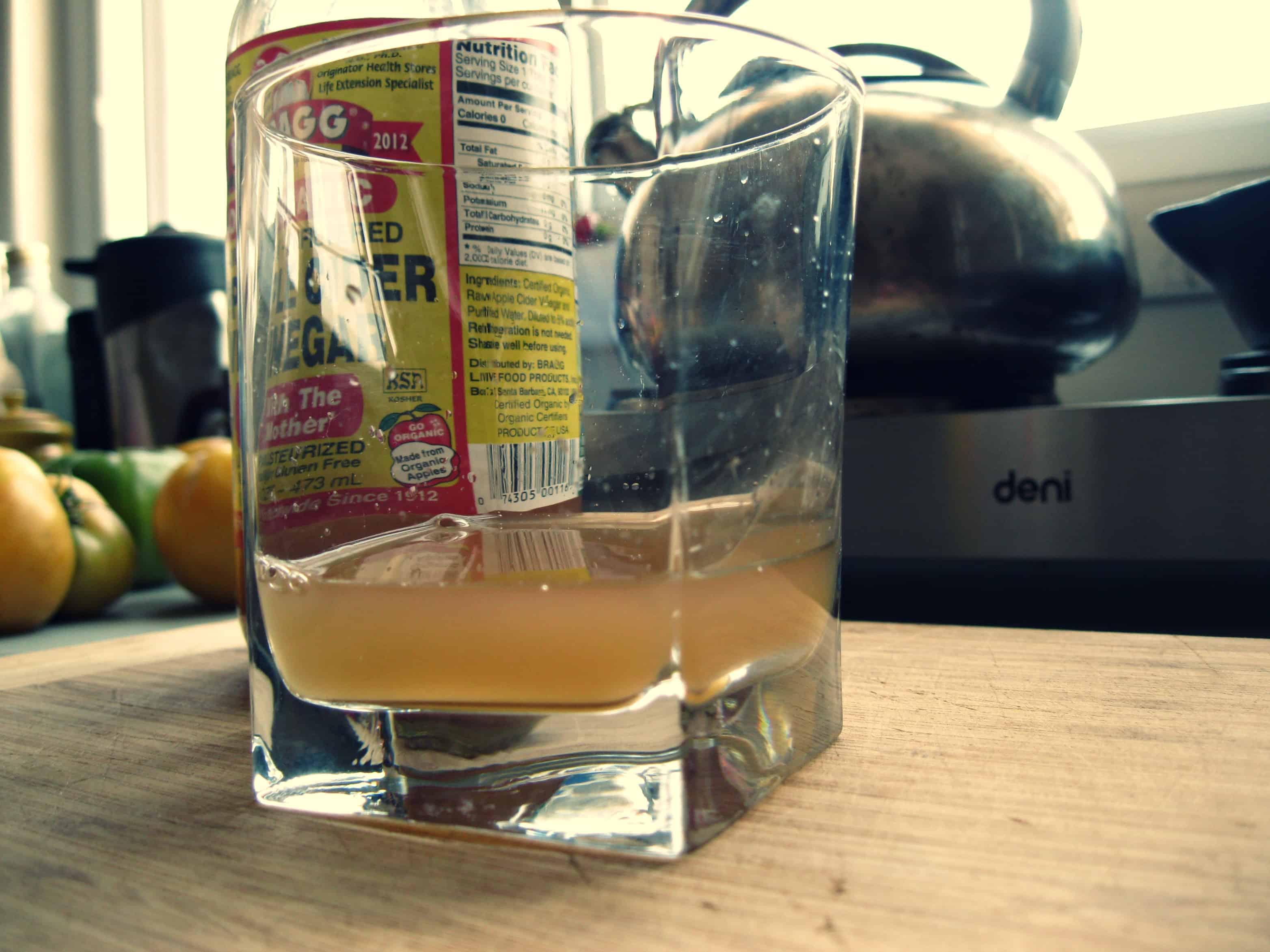 A finger of apple cider vinegar in a rocks glass.