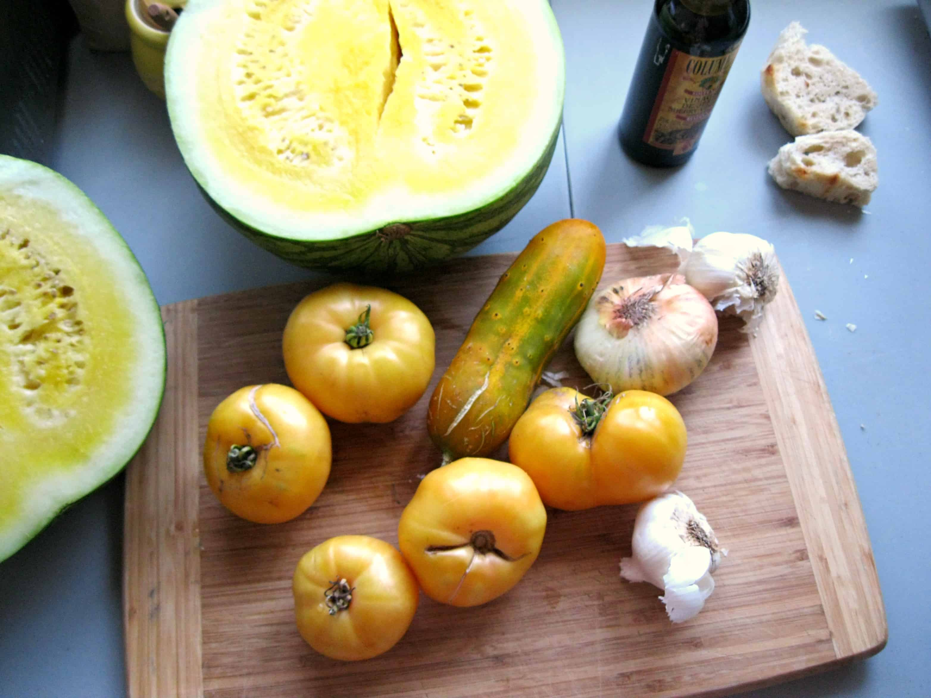 Yellow tomatoes, onions, and yellow watermelon on a cutting board.