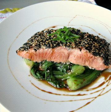 Sesame crusted salmon fillet on top of mini baby bok choy.