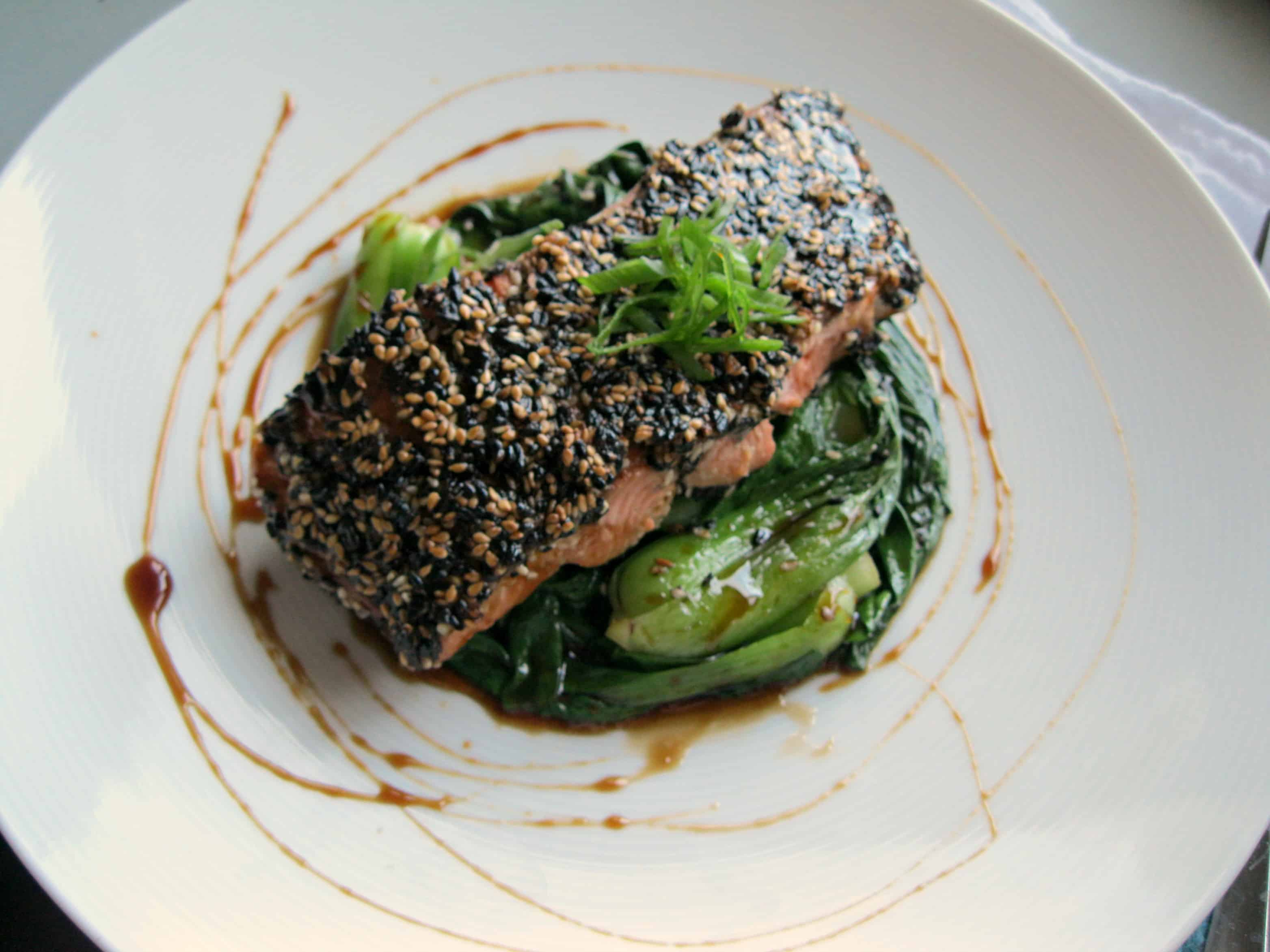 Top view of a sesame crusted salmon fillet over greens in a bowl.