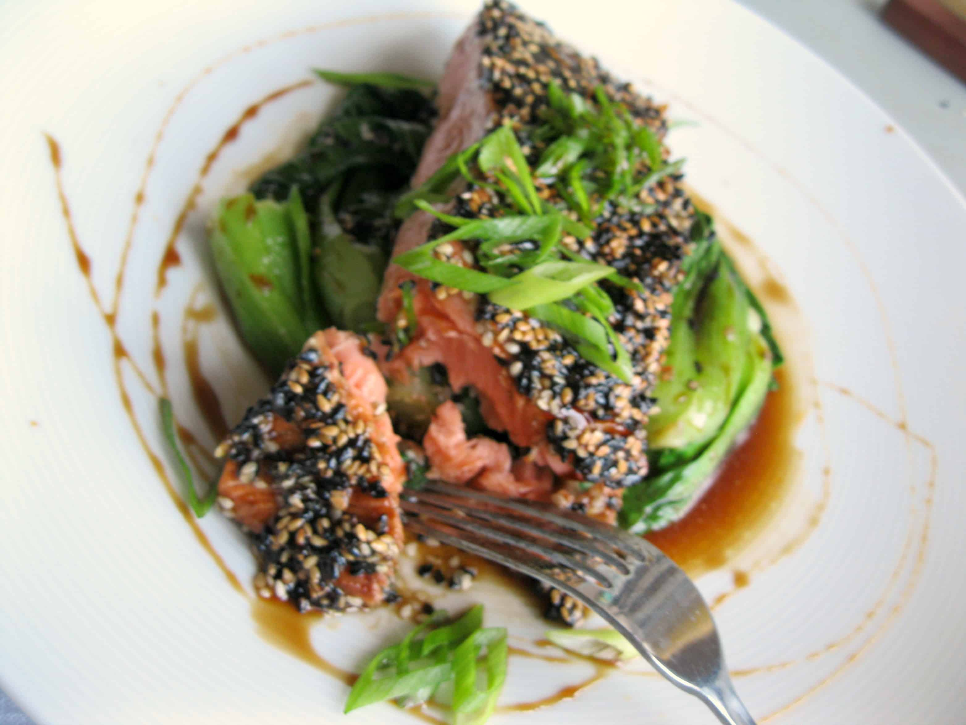 A fork cutting a bit of sesame crusted salmon.