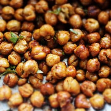 Crispy chick peas on a parchment lined baking sheet.