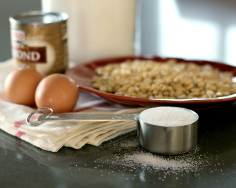 A bowl of pine nuts, two eggs, and a small measuring cup of sugar.