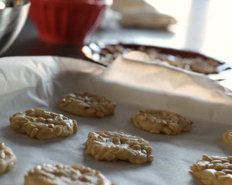 Unbaked pignoli cookie dough on a parchment lined baking sheet.