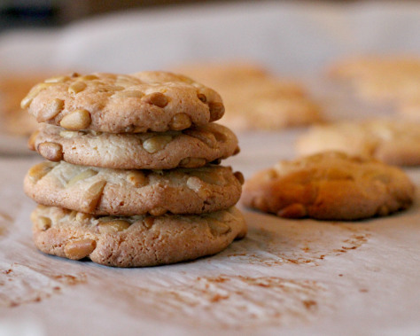 A stack of pignoli cookies on a parchment lined baking sheet.