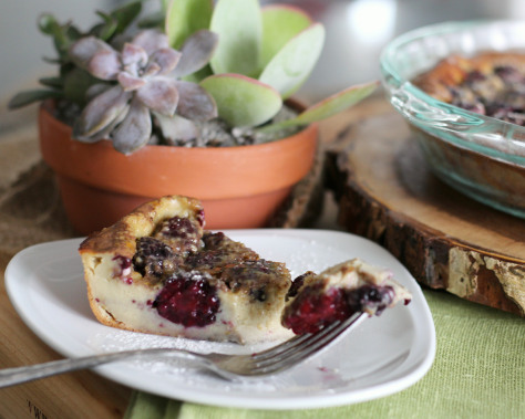 A triangle slice of maple berry clafoutis on a white dessert plate.