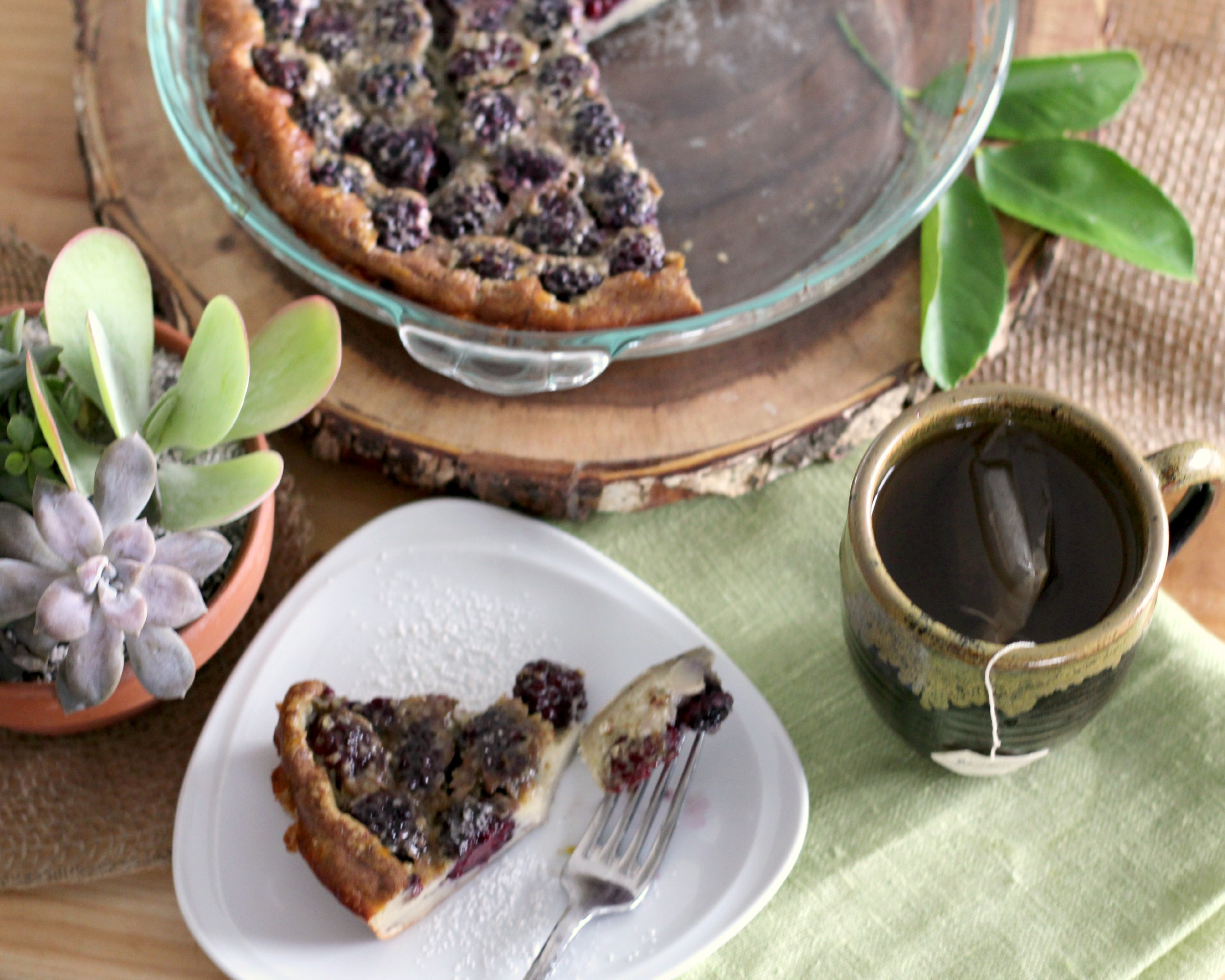 A glass pie plate of maple berry clafoutis with a slice removed to a white dessert plate.