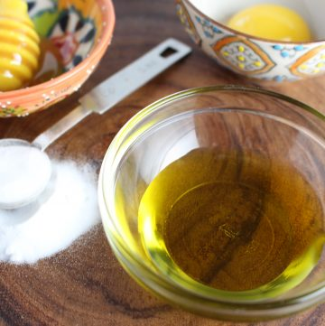 A small glass prep bowl of olive oil ext to a tablespoon of sugar.