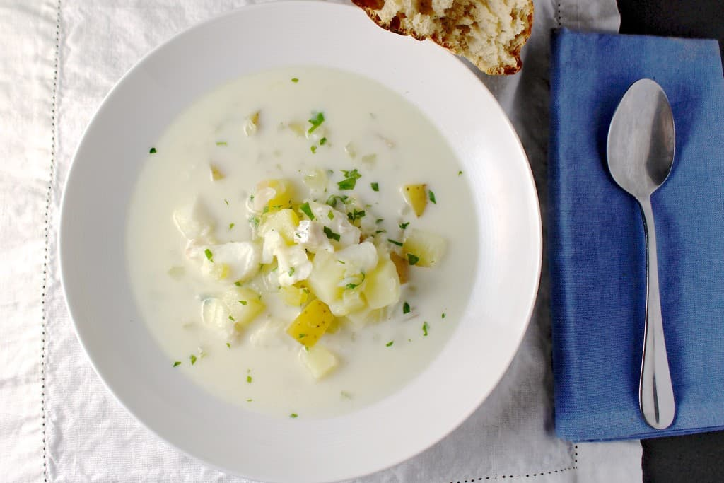 Top view of a shallow white bowl filled with fish and potato chowder.
