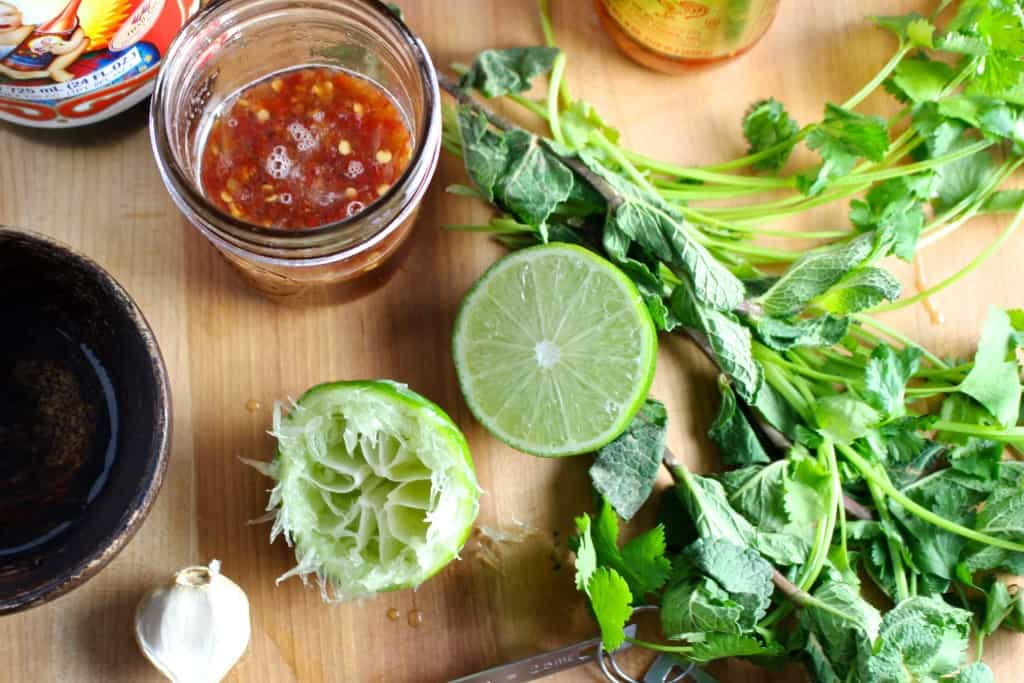 Lime halves, fish sauce, and a bunch of cilantro on a wood board.