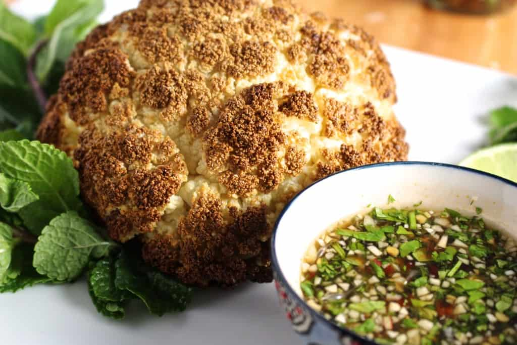 A whole roasted cauliflower head next to a bowl of fish sauce.