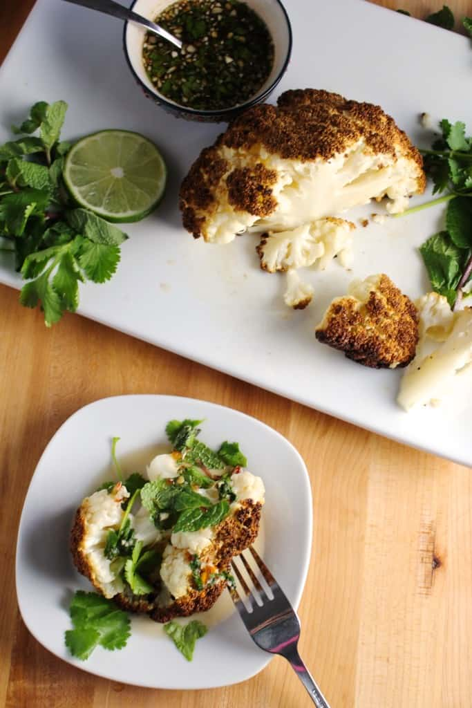 Top view of whole roasted cauliflower head on a white platter with a serving on a small white plate.