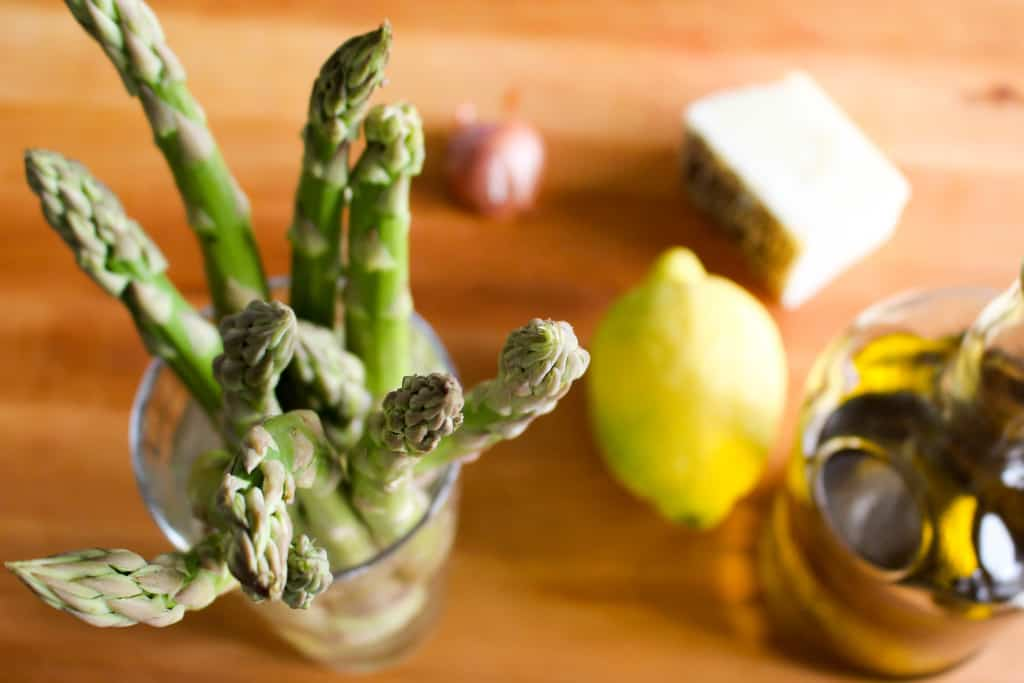 Top view of asparagus spears in a glass next to a whole lemon and shallot.