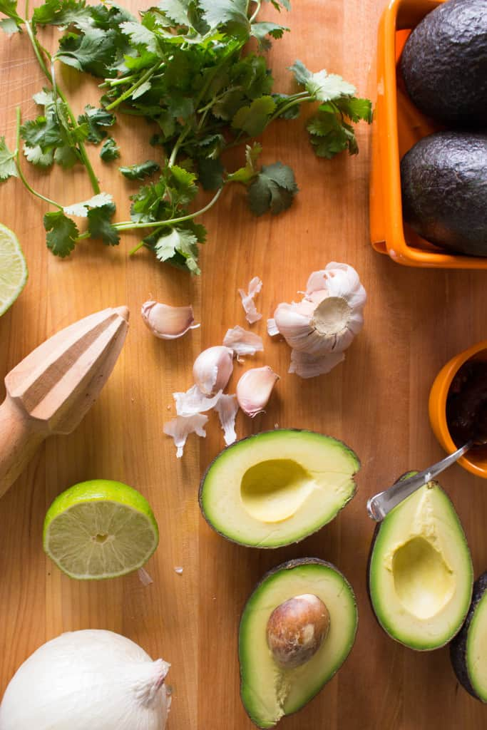 Top view of a wooden table with a citrus reamer, avocado halves, garlic cloves, and cilantro.