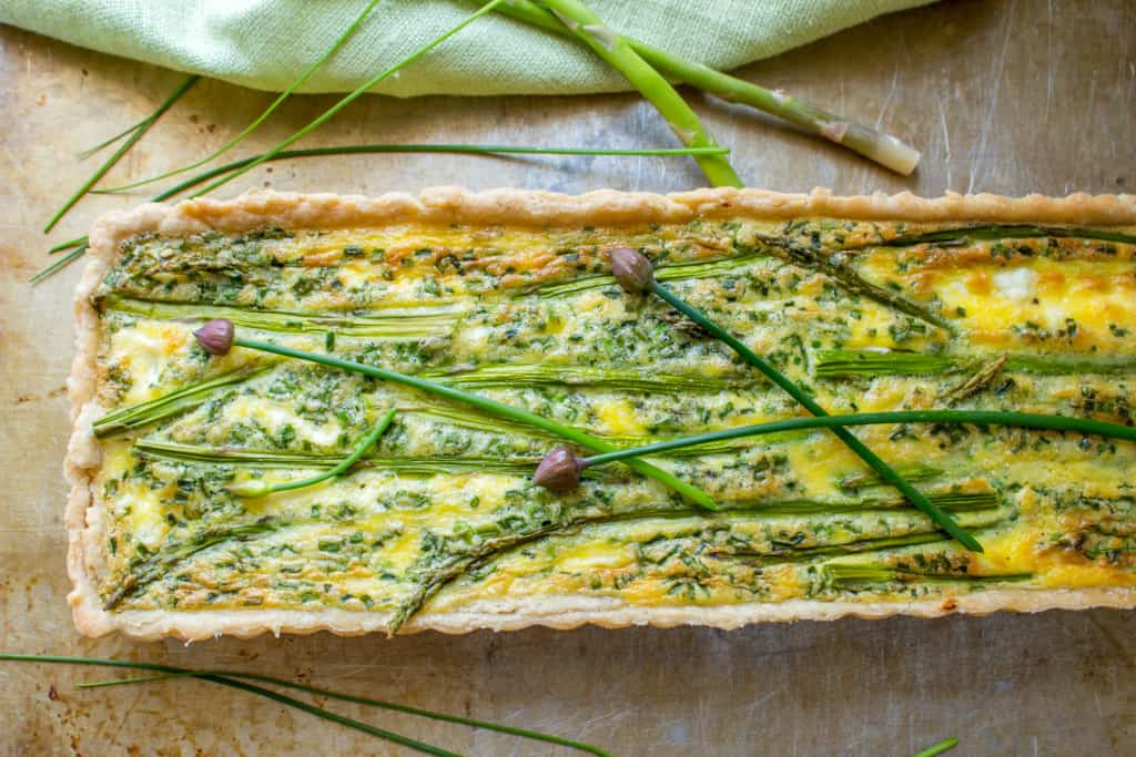 Top view of a rectangle tart shaped asparagus goat cheese tart.