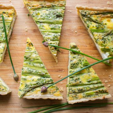 Triangle slices of asparagus goat cheese quiche on a wooden cutting board.