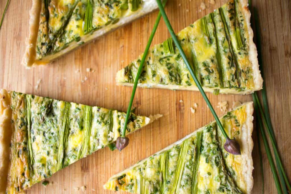 Top view of slices of asparagus goat cheese quiche on a wooden cutting board.