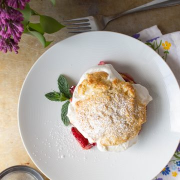 Top view of a strawberry rhubarb shortcake on a white plate.