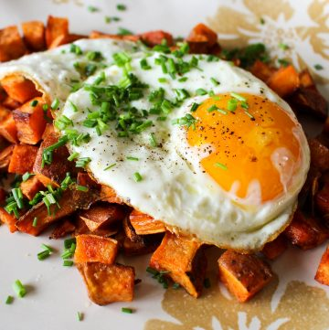 A sunny side up egg over a pile of sweet potato bacon hash.