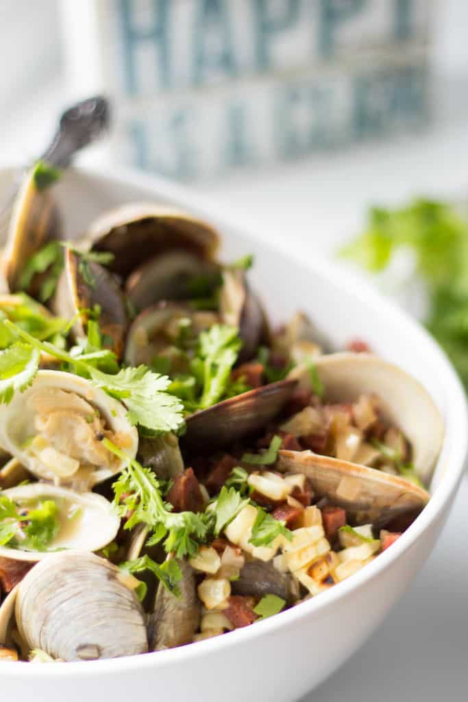 Close up of fresh baked clams that have been topped with fresh corn and crumbled chorizo.
