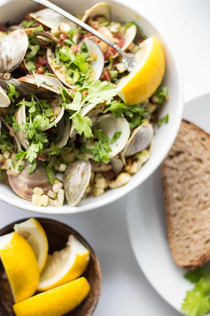 Top view of chorizo and corn topped clams with lemon wedges.