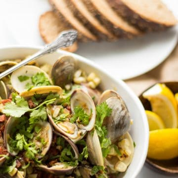 A white bowl of baked clams topped with chorizo, corn, and salsa.