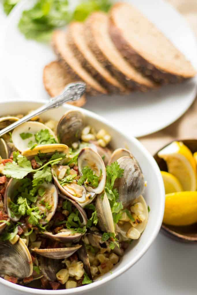 Top view of a bowl of baked clams with a plate of bread slices in the background.