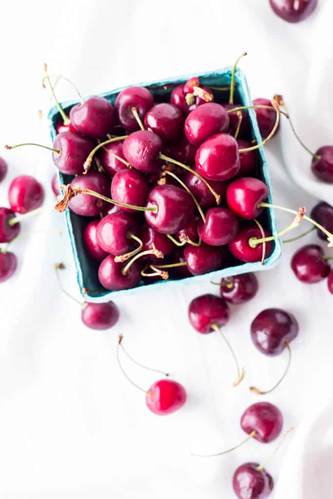 Top view of a pint bin of fresh red cherries with stems.