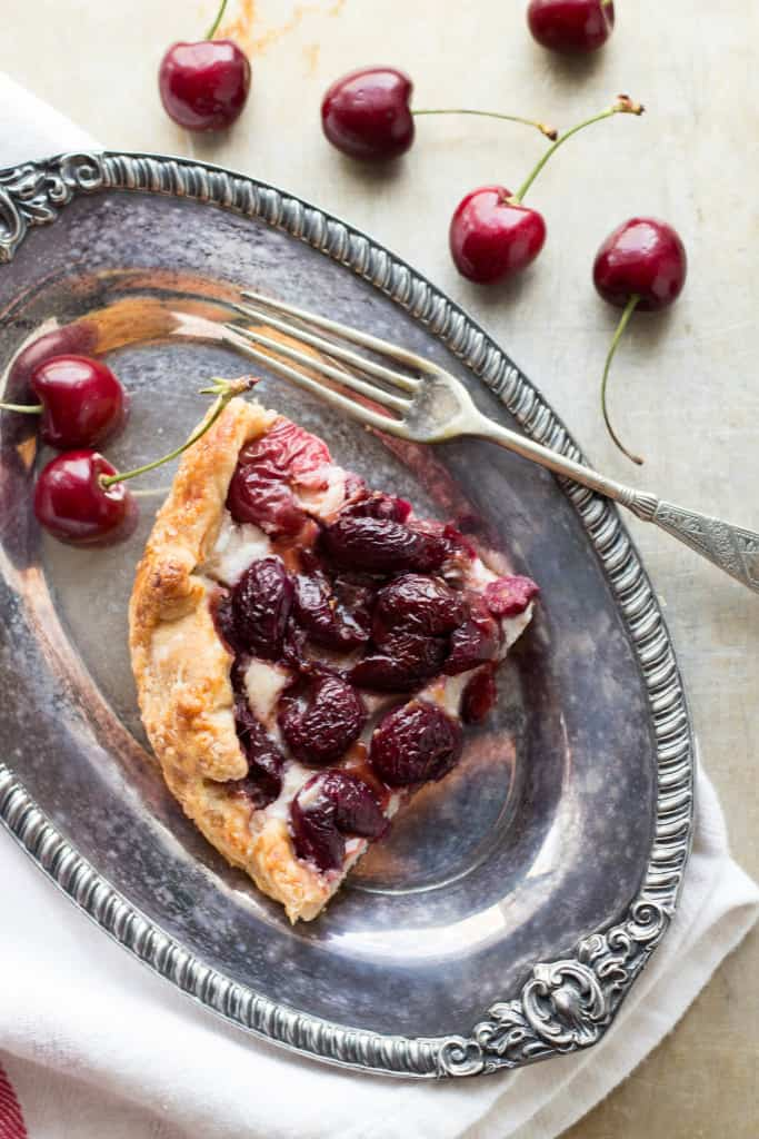 Top view of a corner slice of cherry ricotta tostata on a silver plate with a fork.