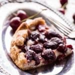 Top view of a slice of cherry vanilla ricotta crostata on silver plate with a fork.