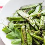 Grilled pea pods in a white bowl.