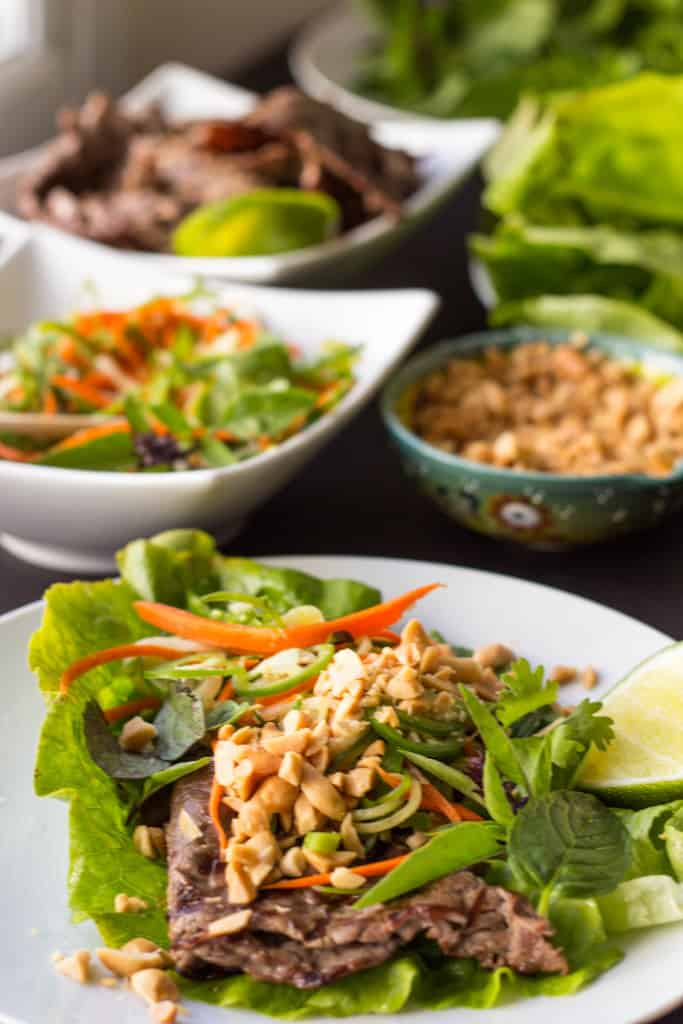 A white dinner plate with a Thai beef lettuce wrap ready to eat and bowls of ingredients in the background.