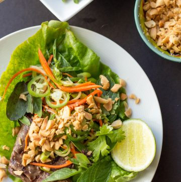 Top view of a large Thai beef lettuce wrap on a white dinner plate.