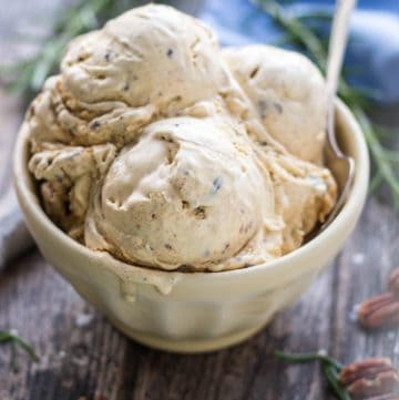Close up of a bowl filled with scoops of brown butter pecan ice cream.