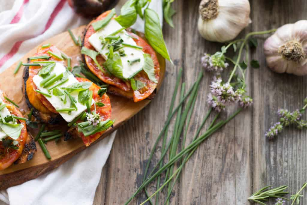 Top view of heirloom tomato toast points next to fresh chives on a wood board.