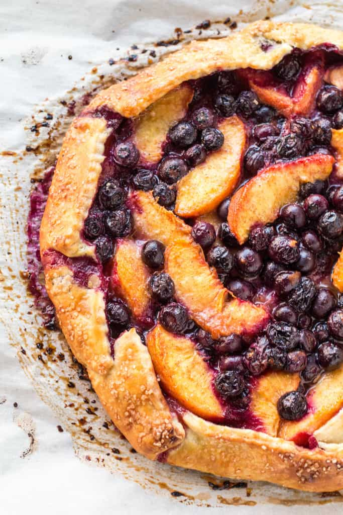 Top view of a blueberry peach crostata on parchment paper.