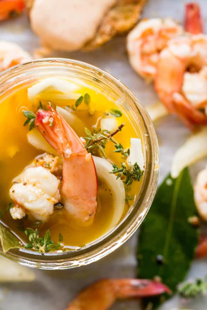 Top view of a mason jar filled with shrimp in pickling liquid.