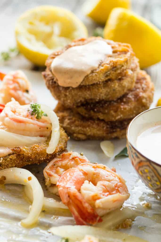 A stack of fried green tomatoes next to pickled shrimp.