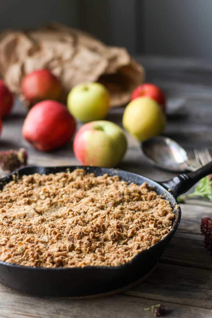 Brown butter apple crisp in a cast iron skillet with fresh apples in the background.