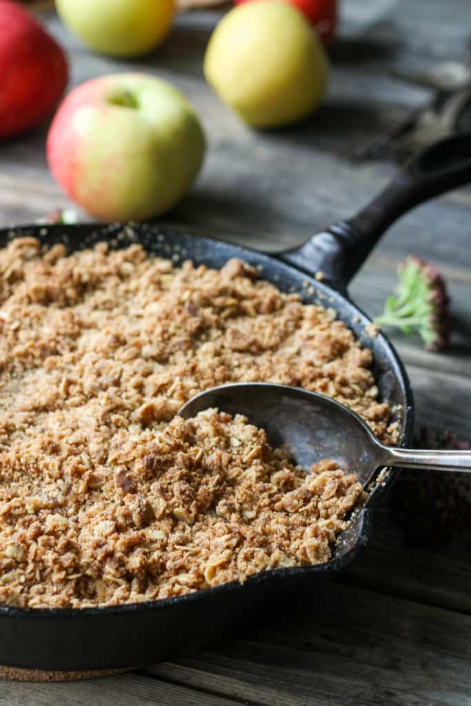 A metal spoon scooping into a cast iron skillet of brown butter apple crisp.