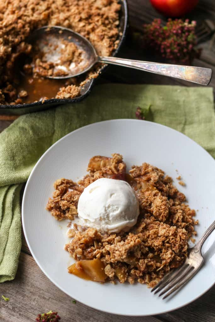 Top view of brown butter apple crisp topped with a scoop of vanilla ice cream on a white dessert plate with a fork.