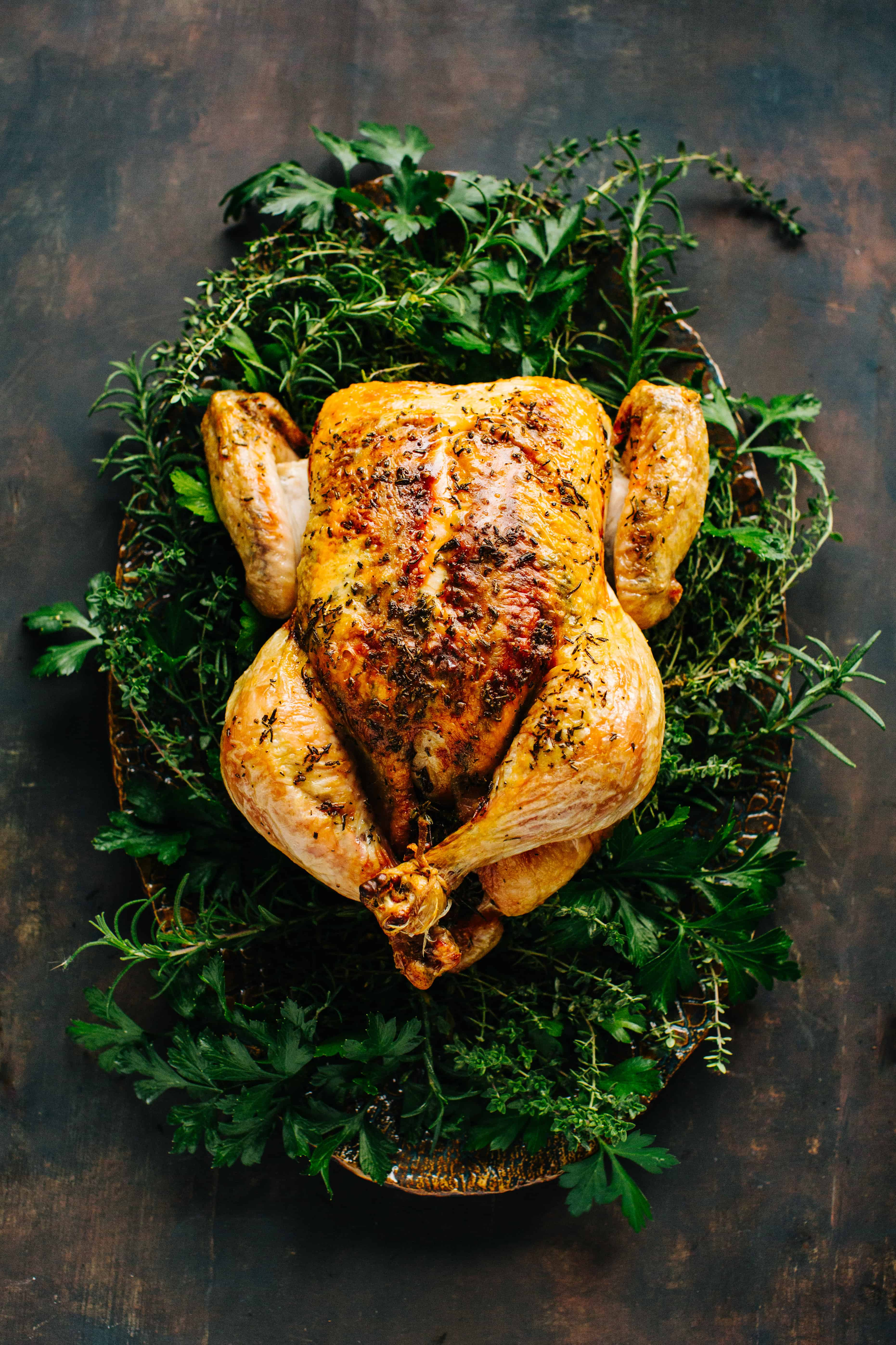 whole roasted chicken on a serving platter surrounded by fresh herbs on dark wood background